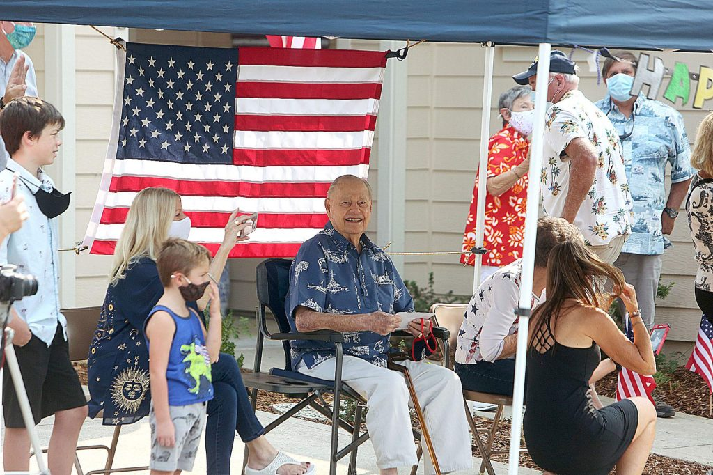 Lou Conter smiles as he's surrounded by his family Saturday morning at his Grass Valley home where he was given a surprise drive by birthday salute for turning 99.