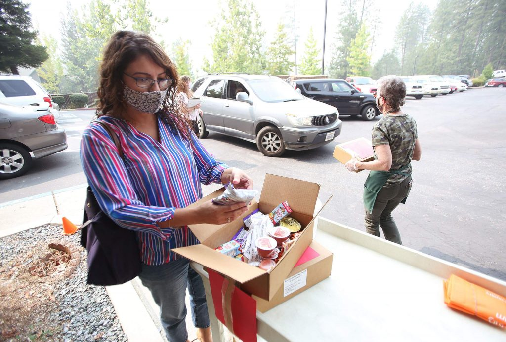 Gold Country Senior Services Executive Director Janeth Marroletti shows off the contents of a five-day emergency meal supply. The rations were being passed out to seniors Wednesday from the parking lot of Nevada City Senior Apartments in Grass Valley. Another giveaway is being planned to coincide with the senior firewood distribution on Oct. 3.