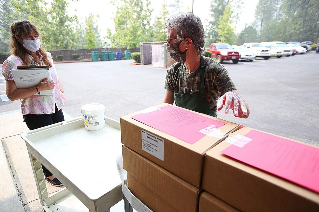 Cynthia Martin (left) and Debby Gray help distribute emergency meal packages to seniors Wednesday from the parking lot of the Nevada City Senior Apartments. The next monthly emergency meal distribution is tentatively being scheduled to coincide with the senior firewood giveaway on Oct. 3.