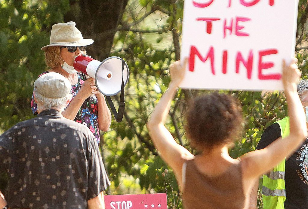 An organizer uses a megaphone to talk to the crowd of protesters gathered against the proposed plans to reopen the idaho Maryland Mine.