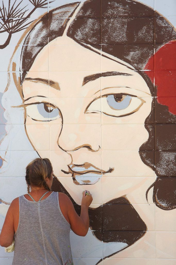 Mural artist Ursula Young adds details to the Lola Montez inspired mural going up along the 100 block of Neal Street Thursday. The mural is slated for completion later today.