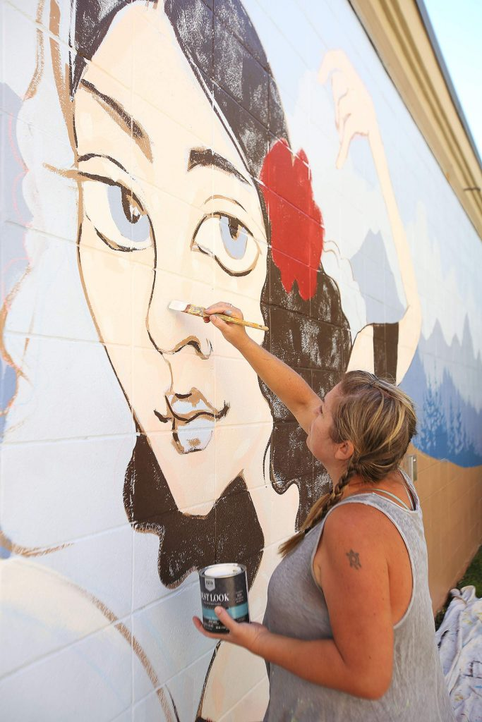 Mural artist Ursula Young adds details to the Lola Montez inspired mural going up along the 100 block of Neal Street on Thursday. The mural is slated for completion today.