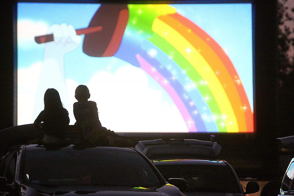 A pair of drive-in movie goers take in Tuesday night's family and children's film shorts atop a vehicle at the Nevada County Fairgrounds.