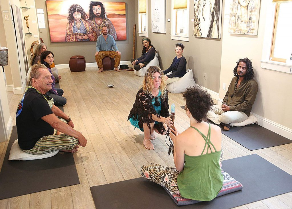 Golden Lotus Gallery and Lounge's Niwan Yod hands a member of the talking circle a crystal, energized to help people clear their throats and speak from the heart.