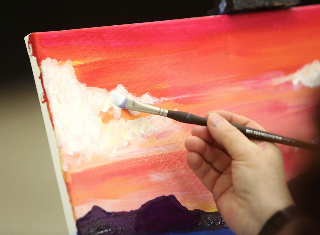 A Come Paint With Us participant works on painting clouds in her skyline during a recent event at The Foothills Event Center where the socially distant paint sessions are offered. No experience is necessary and people get a complimentary drink from the bar.