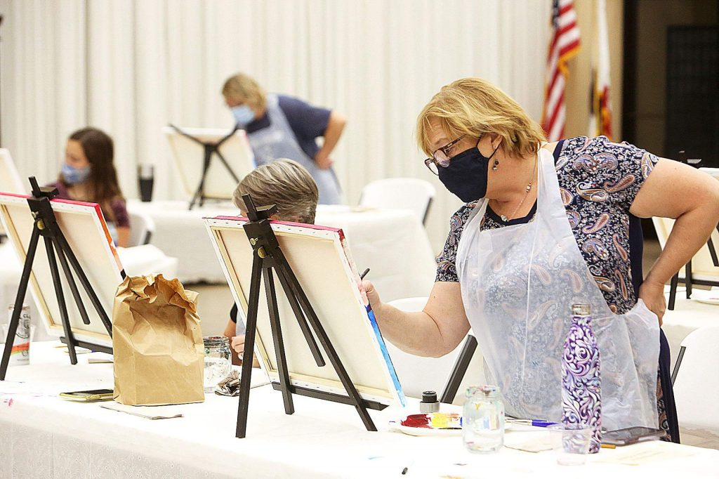 Nevada City's Claire Diament-Turner works on some of the details on her Emerald Bay painting during the most recent Come Paint With Us Event at The Foothills Event Center.