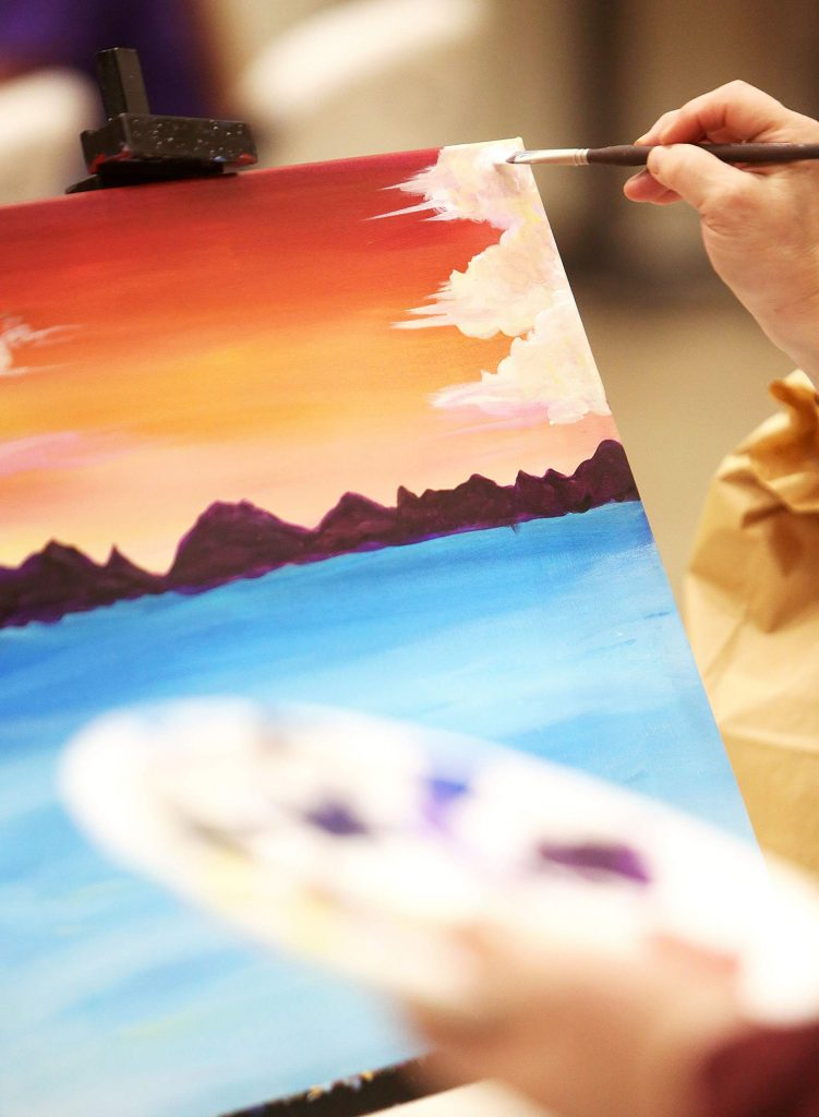 A Come Paint With Us participant works on clouds in her skyline during a recent event at The Foothills Event Center, where the socially distant paint sessions are offered. No experience is necessary and participants get a complimentary drink from the bar.