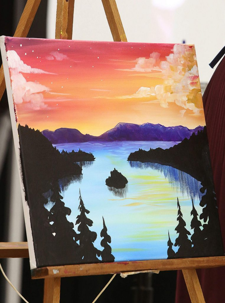 Dorland's finished colorful painting of Emerald Bay is on display during the Come Paint With Us event for students to reference.