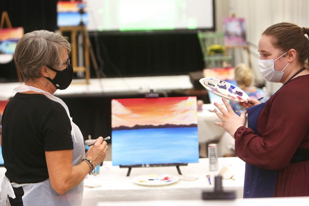 Come Paint With Us instructor Katherine Dorland assists a student during a recent painting event. Participants receive step-by-step guidance while enjoying good company and a complimentary glass of wine, beer, or soda.