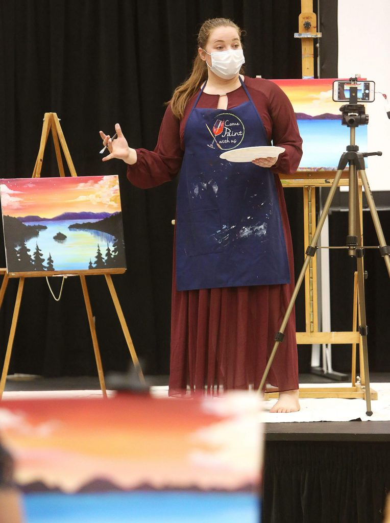 Come Paint With Us instructor Katherine Dorland references her finished piece of Lake Tahoe's Emerald Bay while working on a new version Tuesday evening with students at The Foothills Event Center. The paint-and-sip style event is able to host many people in the socially distant venue.