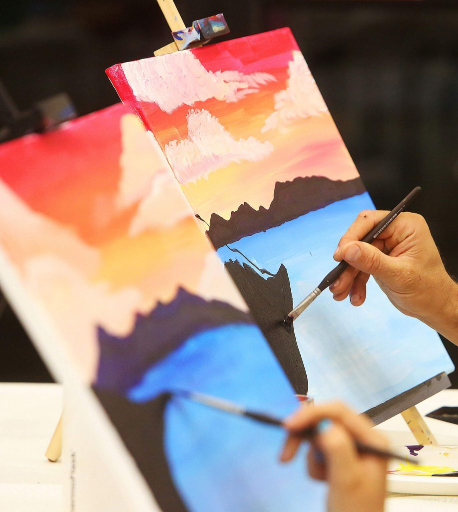 Student artists work on the details of their Lake Tahoe Emerald Bay paintings.