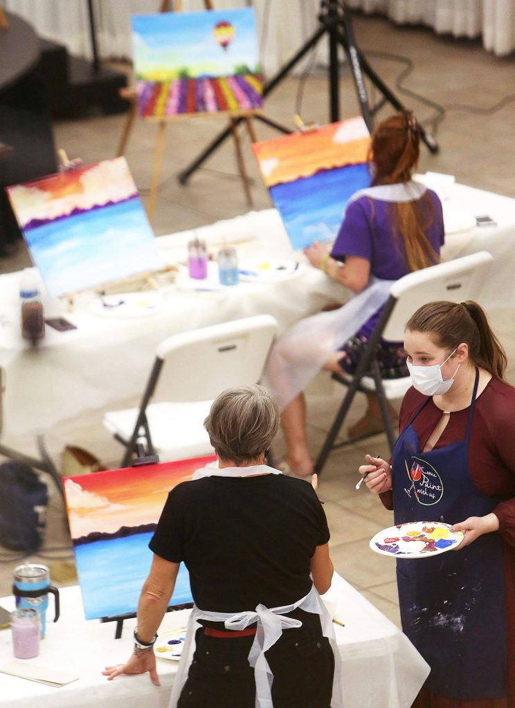 Come Paint With Us instructor Katherine Dorland helps a student during Tuesday evening's painting session. No experience is necessary for the paint-and-sip style experience.