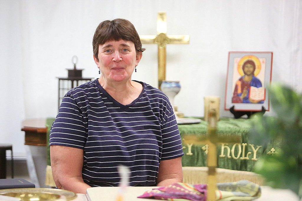 Grass Valley United Methodist Church Pastor Cathy Love sits in front of the sanctuary she has set up for zoom worship services.