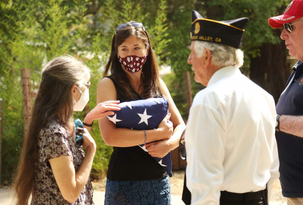 Misti Wood (center) with mother Robin Wood, are approached by members of the American Legion Post 130 following Saturday's Remembrance Day ceremony. The Wood's held a service flag in memory of father/husband Dale Wood, who was a Navy Seabee that died in May and had yet to have a memorial service due to Covid-19.