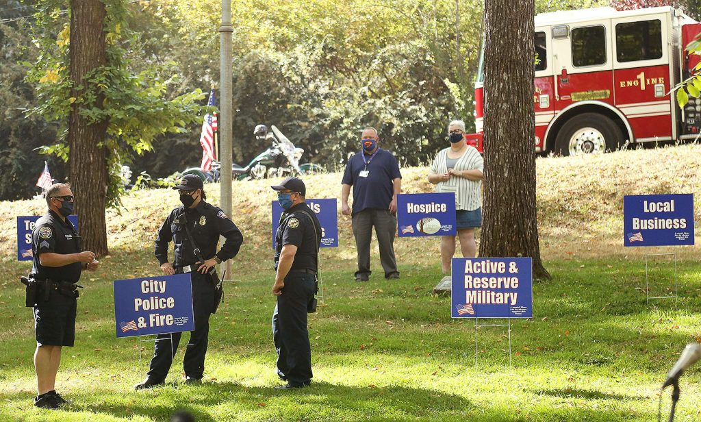 Members of local law enforcement stand among a series of signs placed in Memorial Park during Saturday's Remembrance Day ceremonies to help honor those community members that have been essential in keeping the county operating and moving forward during the pandemic.