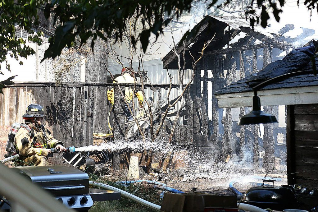 A firefighter douses the charred remains of an outbuilding that burned Tuesday afternoon behind a residence on Marshall Street near West Empire Street. A couple of outbuildings were lost and damage to a garage and residence also occurred.