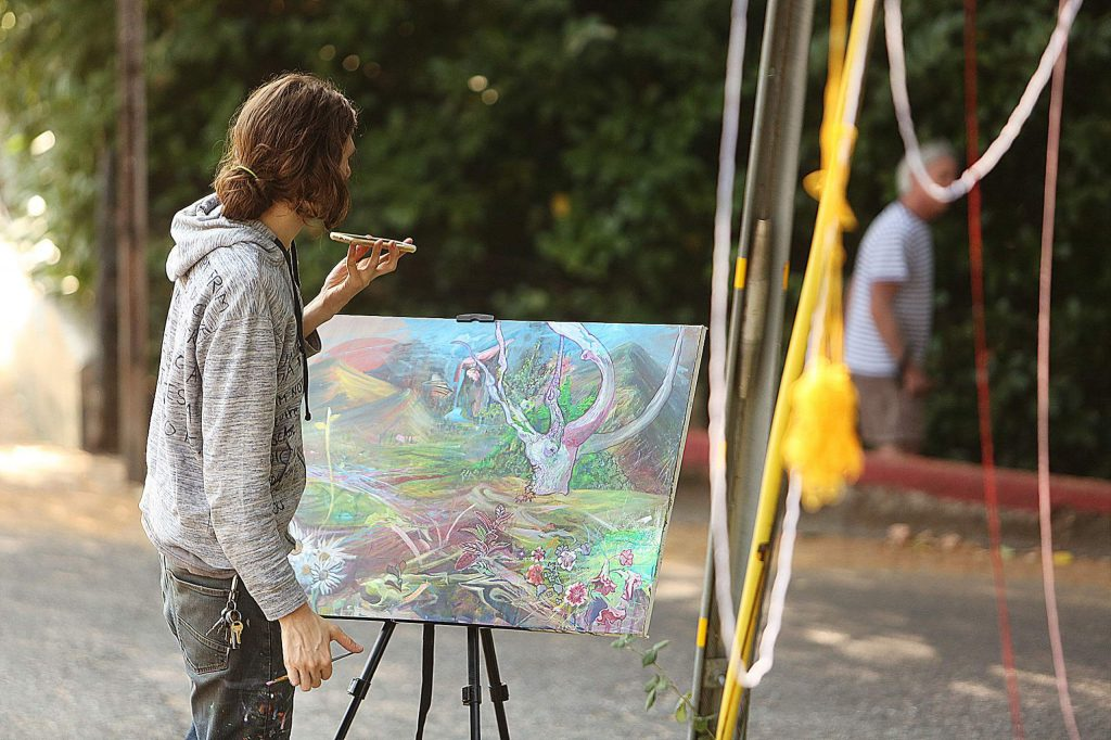 Artist Kyle Kingston works on a painting he's making of the tree and the neighborhood.
