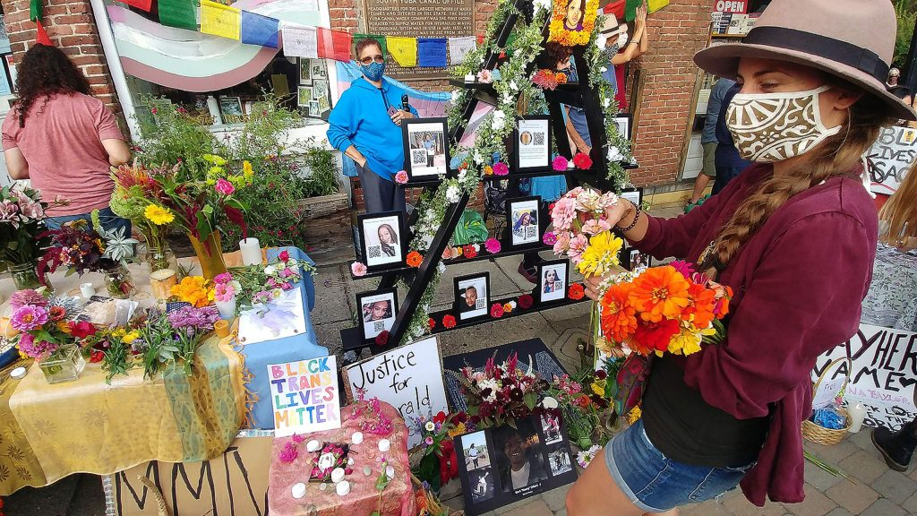People visit a memorial altar set up in Robinson Plaza during Saturday evening's vigil for black lives lost where hundreds of community members showed up to pay their respects.