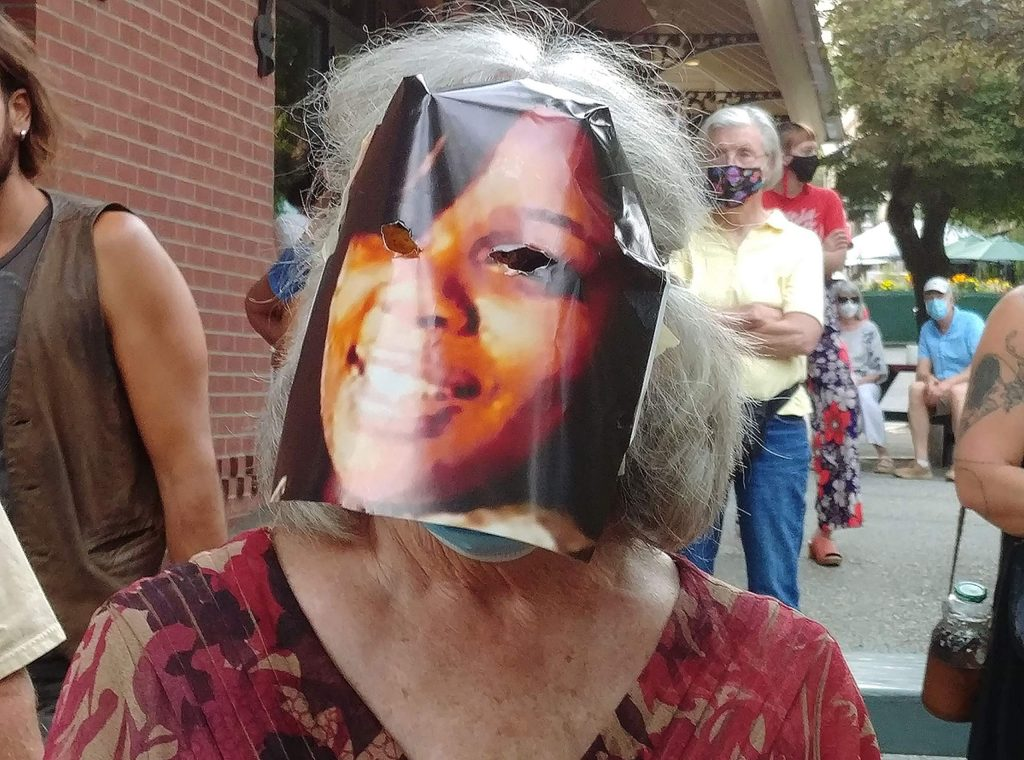 An attendee of Saturday evening's vigil wears a mask depicting Breonna Taylor, who was killed by police in Louisville Kentucky March 13.
