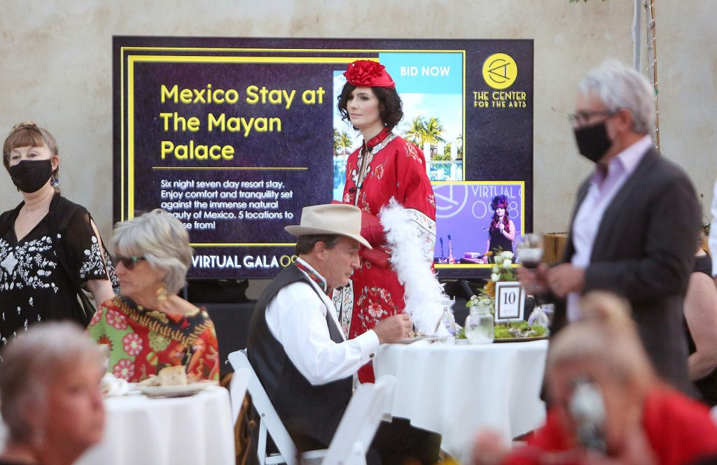 """Virtual Gala attendees arrive to the """"backup bar"""" at the Center for the Arts while folks use their cell phones to place bids during the virtual auction for items such as a Mexico stay at The Mayan Palace."""