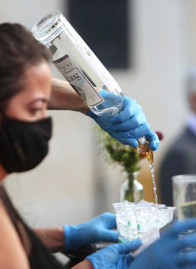 """A bottle of South Fork Vodka flows as drinks are ordered from the virtual gala's """"backup bar"""" set up on the patio behind the Center for the Arts' main stage."""