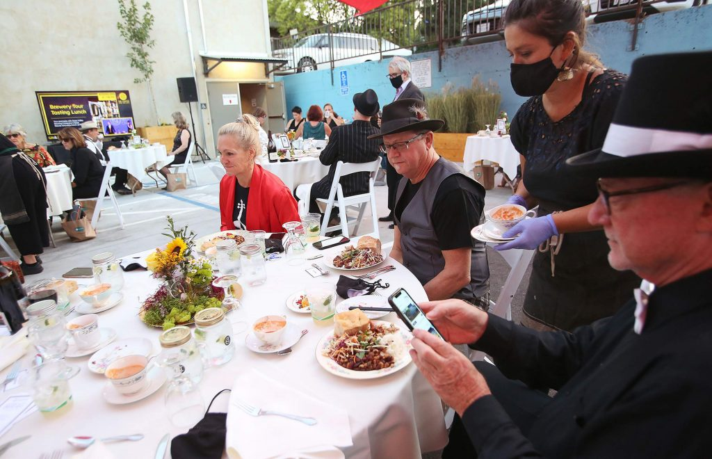 """Dinner is served to the """"backup bar"""" as folks use their cell phones to place bids during the 2020 Center for the Arts virtual gala."""