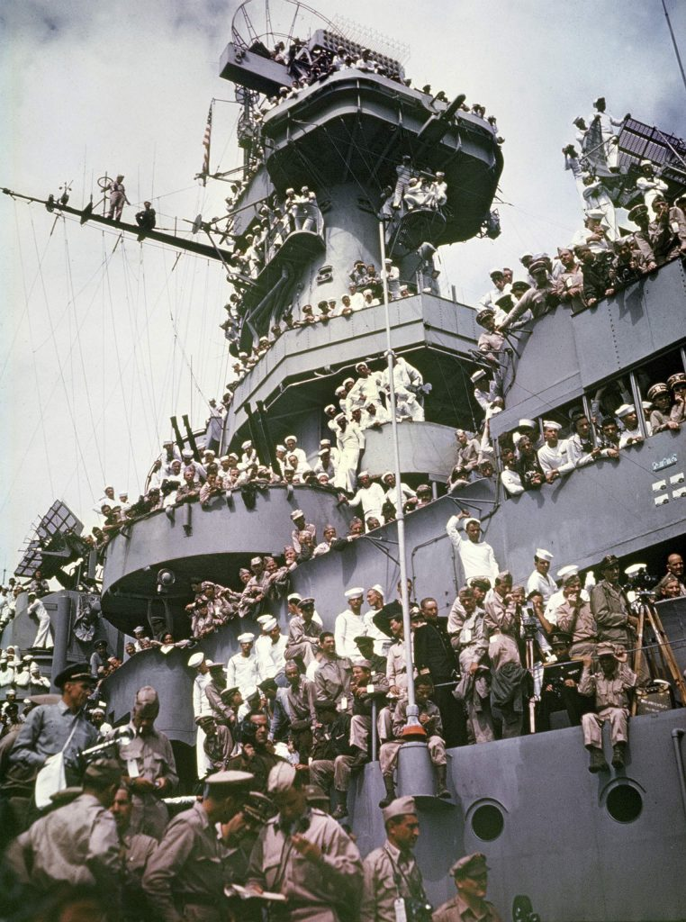 Servicemen, reporters, and photographers perch on the USS Missouri for the onboard ceremony in Tokyo, in which Japan surrendered, ending World War II.