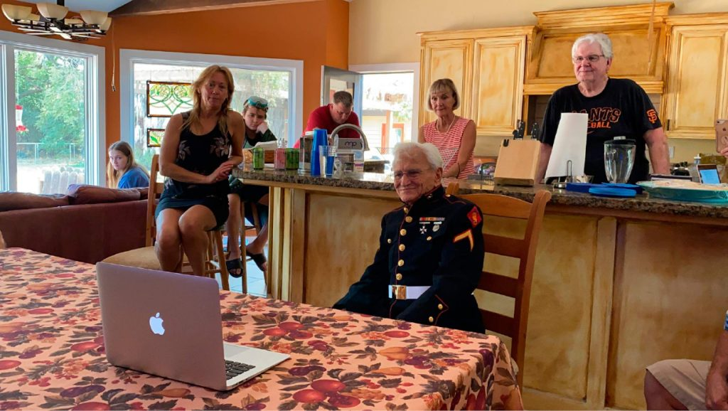 Jerry Pedersen, center, watches a livestream of the 75th anniversary of the end of WWII at his son's home in West Sacramento. Pedersen, 95, was a U.S. Marine on the deck of the Missouri witnessing the end of World War II.