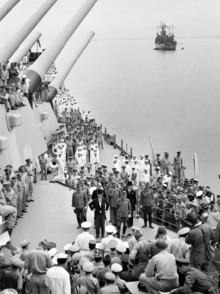 Japanese officials stand in a group facing representatives of the Allied armed forces prior to signing the surrender agreement on the deck of the USS Missouri in Tokyo Bay, during the surrender ceremony marking the end of World War II