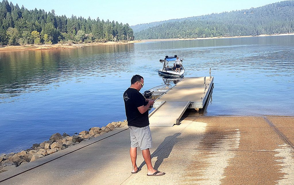 Robert Caslava gets ready to tie off his boat at the Cascade Shores boat ramp after waterskiing with wife Sue and son Kevin, as Chris Brancato, foreground, gives his drone a workout over Scotts Flat Lake on the first day of fall.