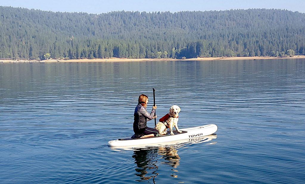 A paddleboarder and her dog take advantage of a sunny, cool morning on the first day of fall at Scotts Flat Lake.