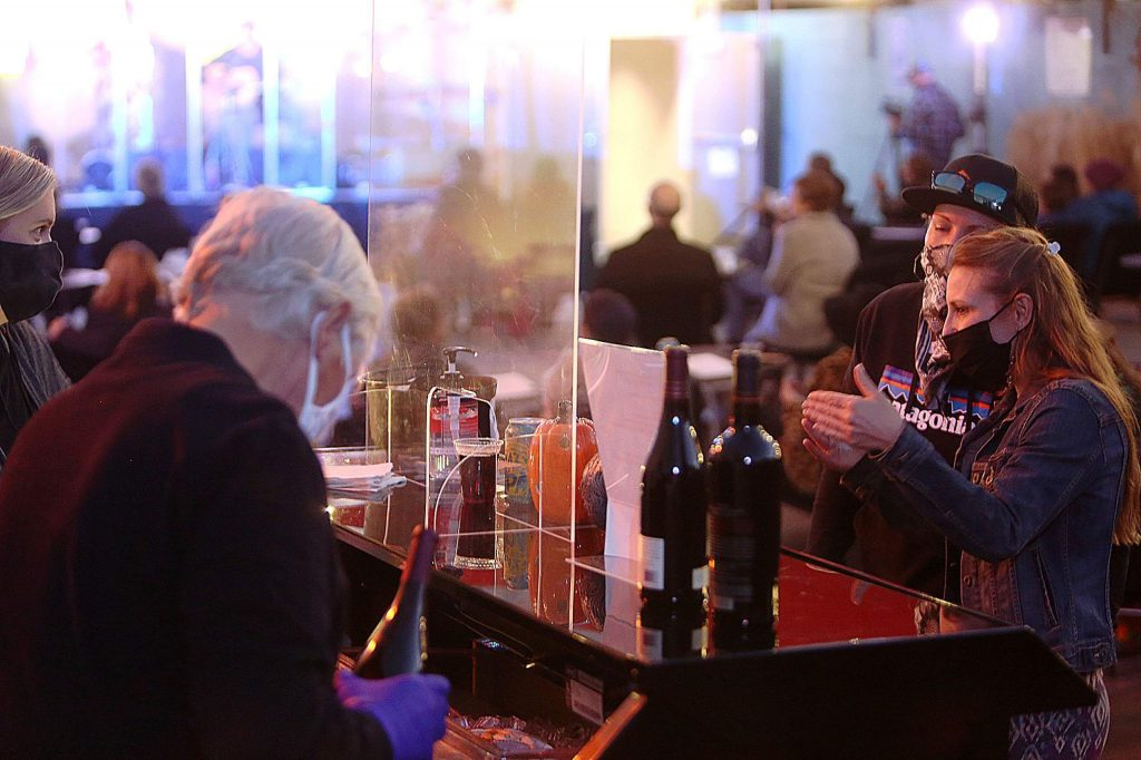 People order drinks from the Backstage Bar, located outdoors behind the main stage of The Center for the Arts while acoustic band Dead Winter Carpenters plays on the outdoor stage. People can also order food, make reservations, as well as pre-order food and beverages.