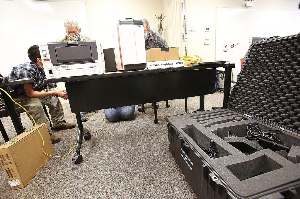 Nevada County elections employees work on setting up the voting center on Friday.