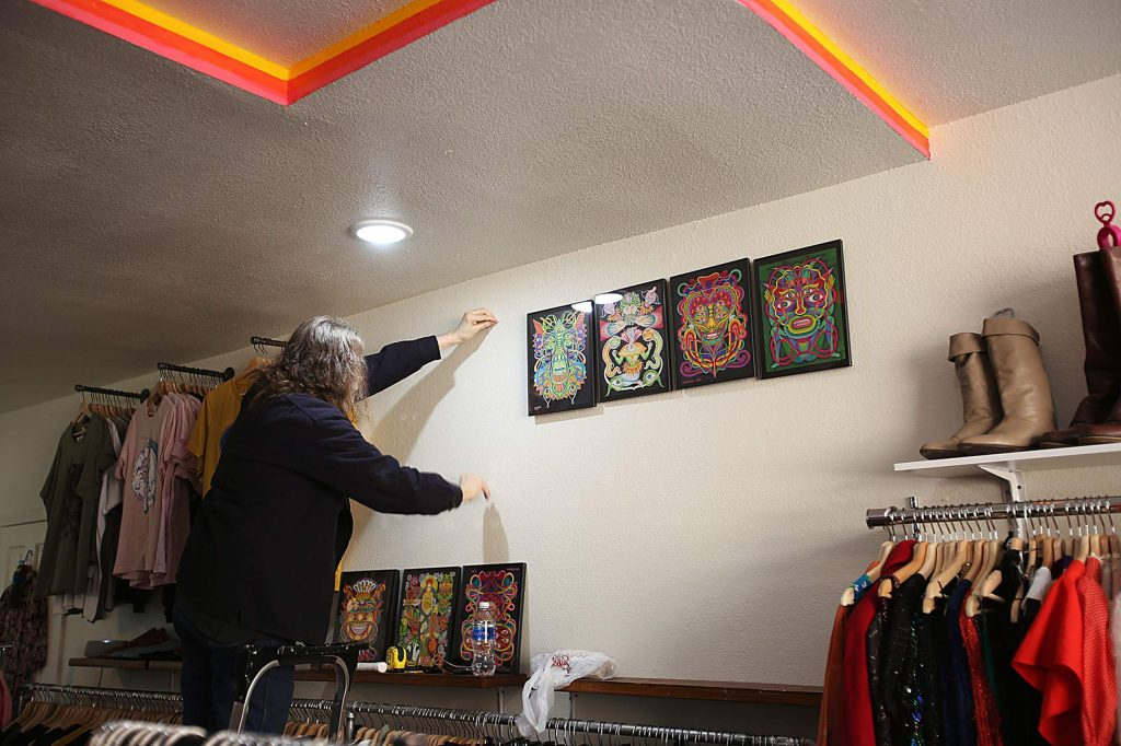 Artist George Parsons begins placing his artwork on the walls at Cosmic Shark in Grass Valley last week for the month-long art show.