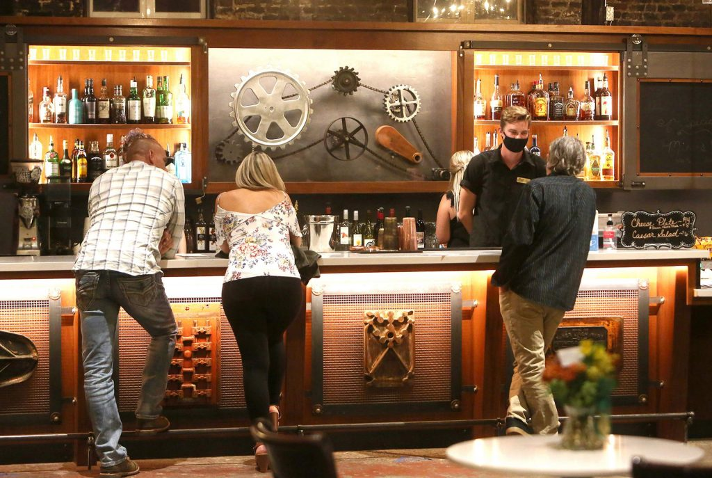 Bartending staff serve customers at the Miner's Foundry's newly renovated Foundry Bar while a comedy and music show go on outside.