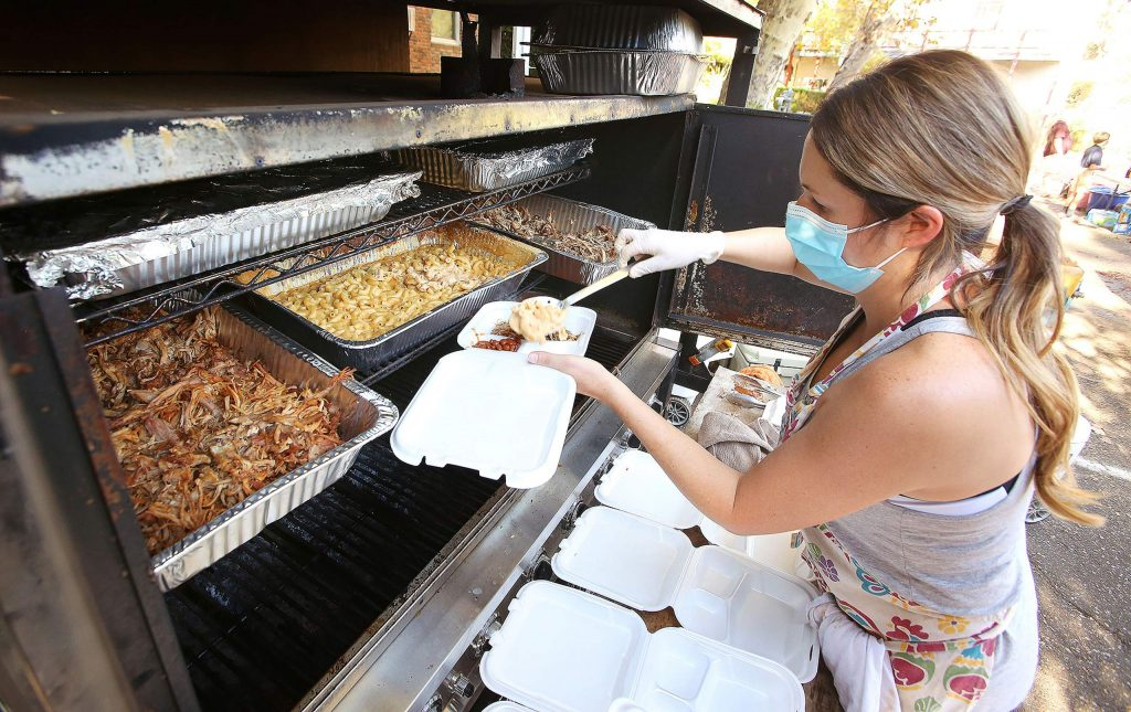 Mount St. Mary's Academy parent Lisa Jackson uses a Bills Chuckwagon catering trailer to help dish up Thursday's pulled pork sandwich meals. Bills Chuckwagon also donated the meat used in the sandwiches.