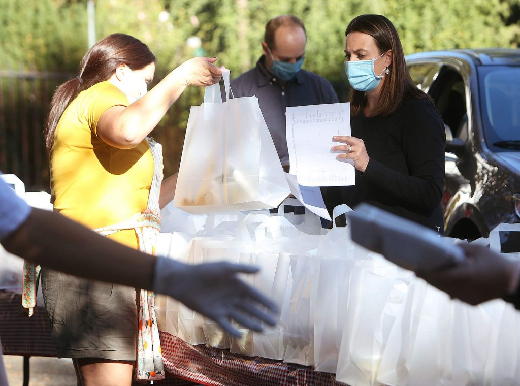 Volunteers help dish out pulled pork sandwich family orders Thursday from the Mount St. Mary's Academy parking lot. Over 600 meals were ordered in advance.