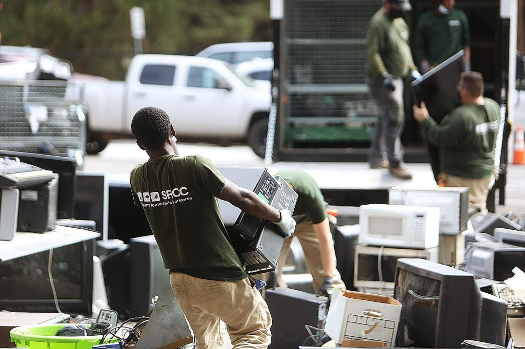 Sacramento Regional Conservation Corps workers help to categorize and load e-waste items into cargo trucks to be shipped to the recyclers.