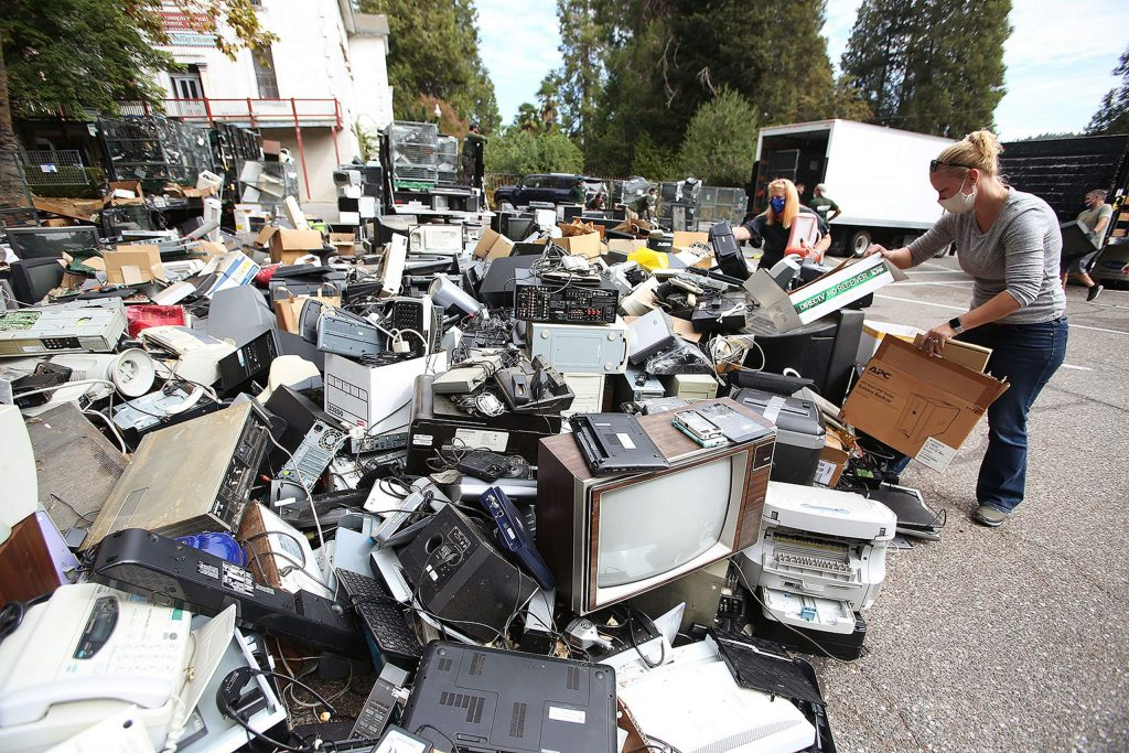Mount St. Mary's Academy e-waste volunteer Krysta Blake pulls trash from the ever growing pile of electronics being collected during the annual recycling event, with proceeds to benefit the school.
