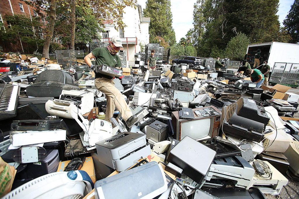 An e-waste worker wades through a sea of electronic items dropped at Mount St. Mary's Academy for its annual recycling event. A portion of proceeds earned go back to benefit the school.