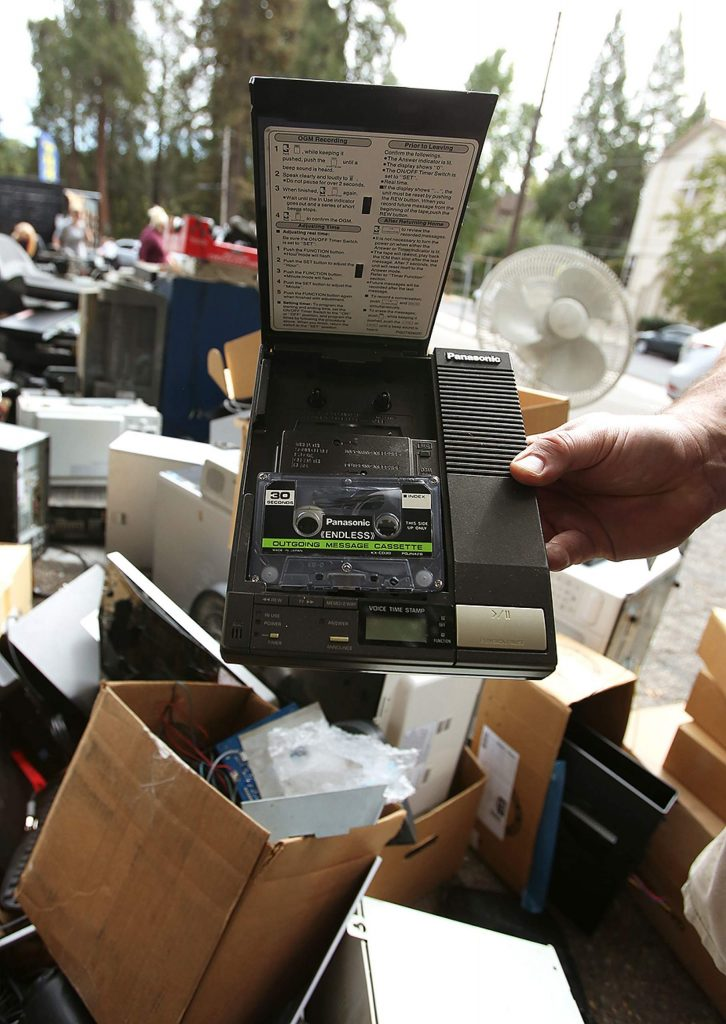 An e-waste worker shows off a donated e-waste item, an answering machine.