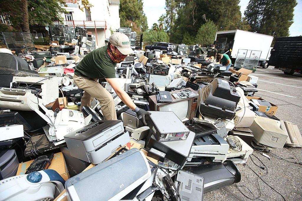 An e-waste worker wades through a sea of electronic items dropped off at Mount St. Mary's Academy for its annual recycling event. A portion of proceeds earned go back to benefit the school.