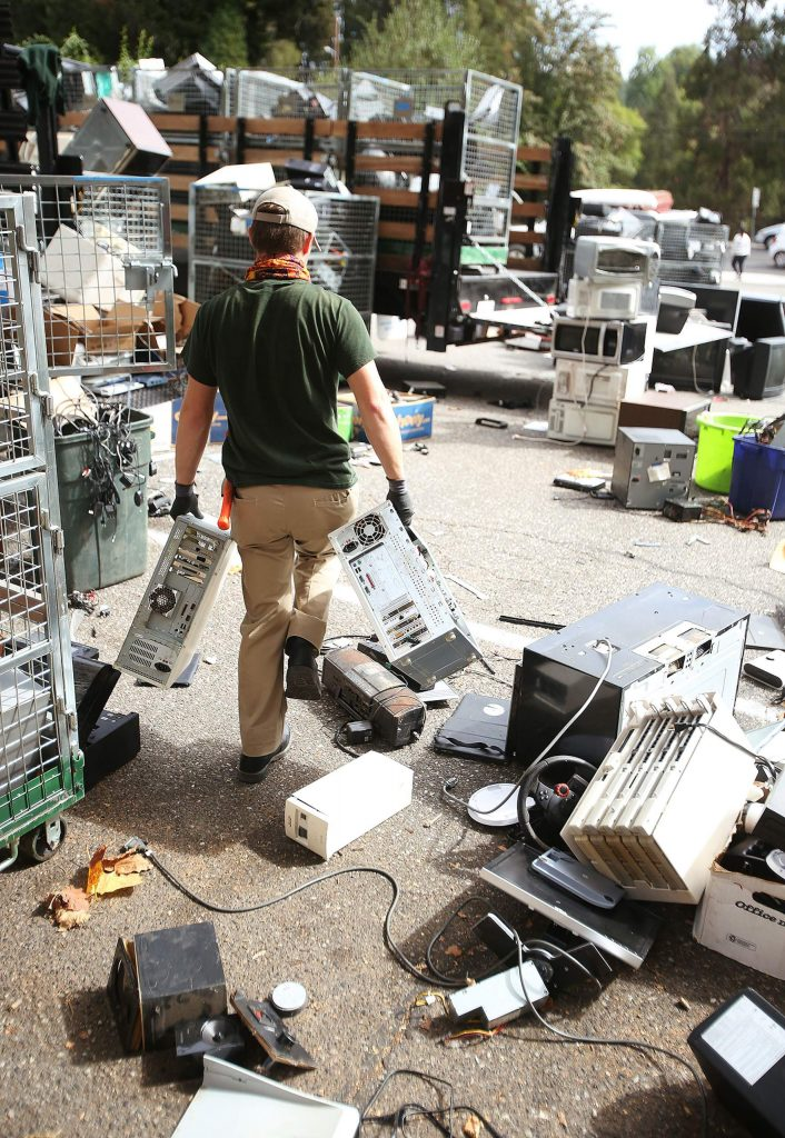 A worker walks through a wasteland of every electronic household item imaginable in the Mount St. Mary's Academy parking lot during the school's annual e-waste fundraiser held Saturday.