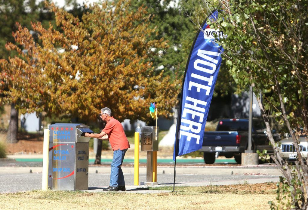 A 2020 voter drops off a ballot in the drop box in front of the Eric Rood Administrative Center Friday.