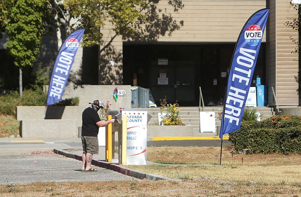 People walk up to the drive-thru ballot drop box at the Eric Rood Administrative Center in Nevada City.