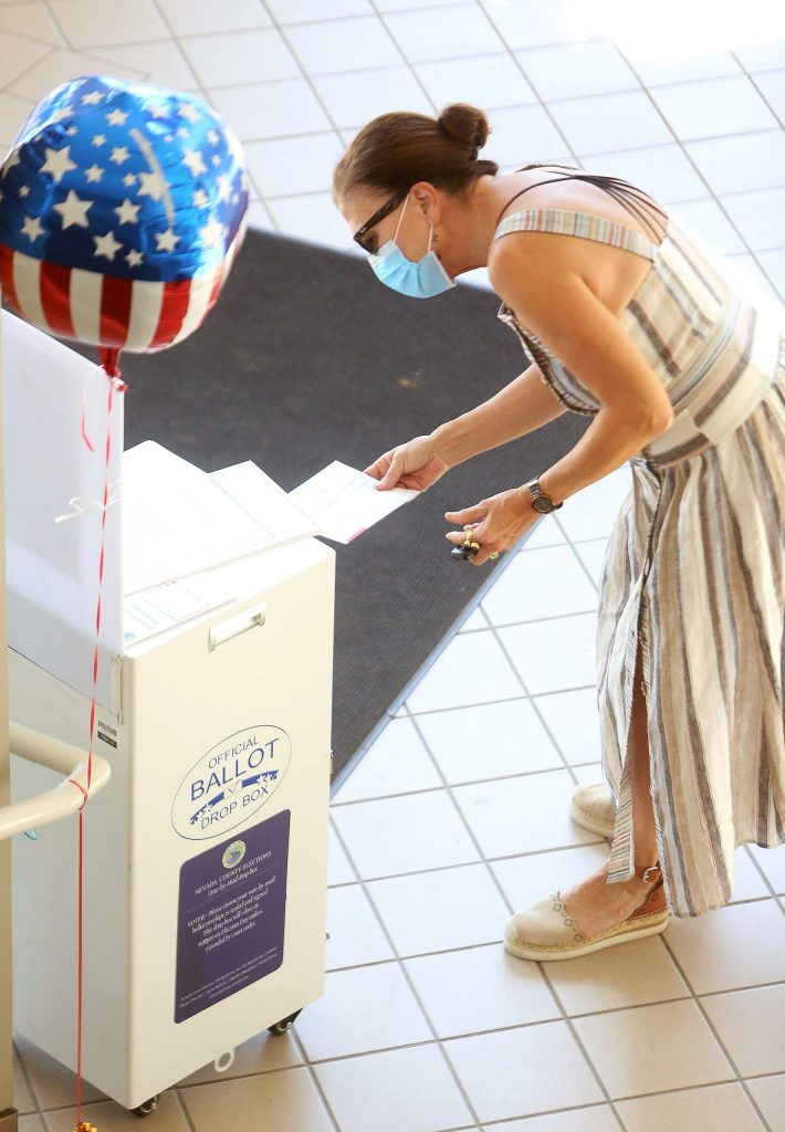 Grass Valley's Lisa Malsam drops off her ballot in the lobby of the Eric Rood Administrative Center Friday morning.