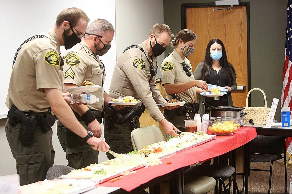Nevada County sheriff's patrol deputies dig in for a portion of the 12 feet of burrito from Maria's during Tuesday's lunch, courtesy of the Grass Valley Elks Lodge.