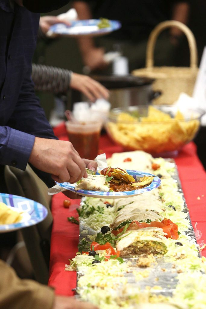 Nevada County sheriff's staff dig in to the 12 feet of burrito during lunch courtesy of the Grass Valley Elks Lodge, whose members wanted to continue their tradition of giving back.