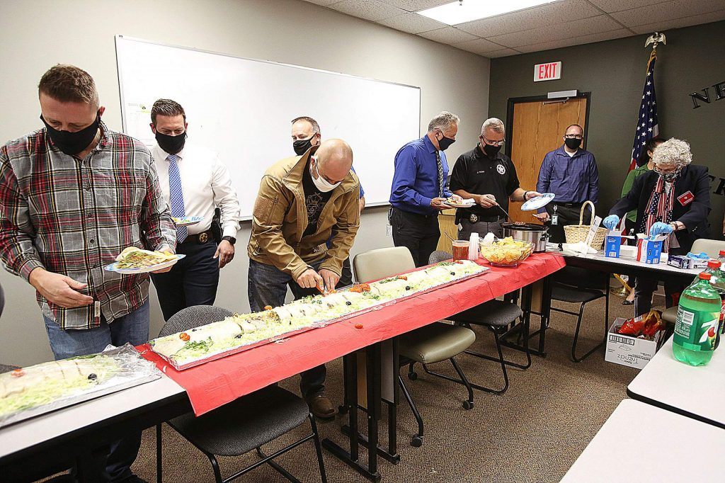 Nevada County sheriff's personnel serve themselves lunch Tuesday. Some of the 12 feet of burrito were set aside for the night shift to eat.