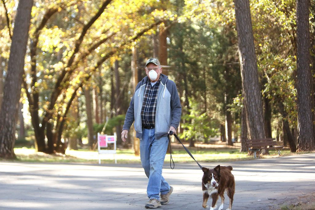 Grass Valley's Joe Streng walks his dog Scarlet Wednesday among the pines at the Nevada County Fairgrounds, its first day reopened to the public following the initial COVID-19 shutdown in March.